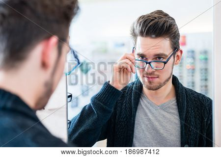 Man testing glasses in optician shop mirror