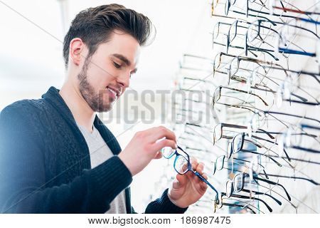 Man in front of shelf with glasses in optician shop looking at camera