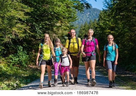Family with four kids hiking in the mountains standing on path