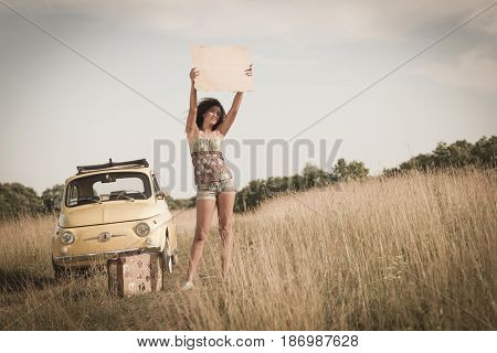 Mixed race woman holding sign near car in field