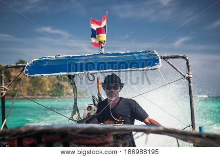 KO PHI PHI, THAILAND, February 2, 2014: Boatman taking tourist to the the beaches of Ko Phi Phi archipelago, Andaman Sea, famous tourist destination in Thailand