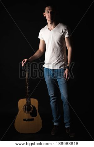 Guitarist, Music. A Young Man Stands With An Acoustic Guitar On A Black Isolated Background. Vertica
