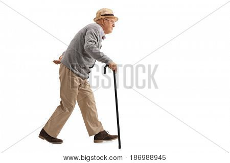 Full length profile shot of a senior walking with a cane isolated on white background