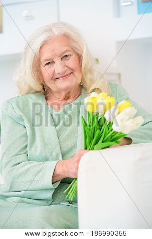 Beautiful senior woman at home with a bouquet of tulips. Happy Mother's Day. Beauty, fashion. Happy retirement.
