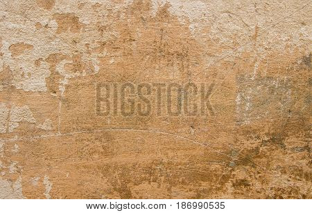 The concrete wall is covered with beige facing filler. On the old wall there are scratches and rubs of various sizes.