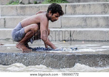 Varanasi India september 19 2010: Indian man making laundry in ganges river in Varanasi.