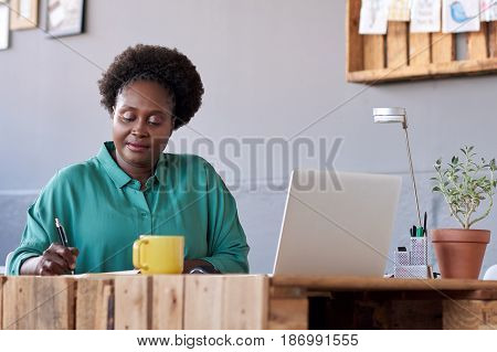 Content plus size African businesswoman casually dressed working on a laptop and writing down notes in a book, while working at her desk in a large modern green and grey office