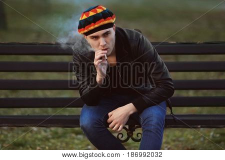 Young man smoking weed while sitting on bench outdoors