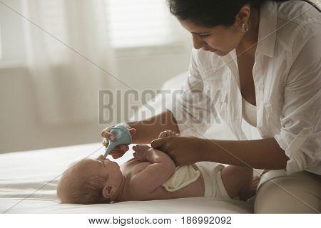 Hispanic mother tending to baby girl