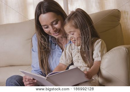 Chilean mother reading book to daughter
