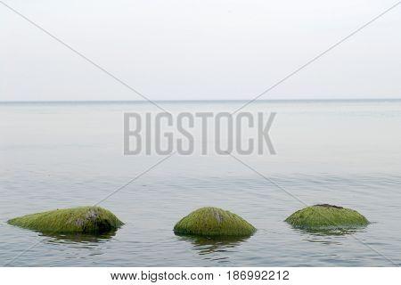 three green stones in the calm sea