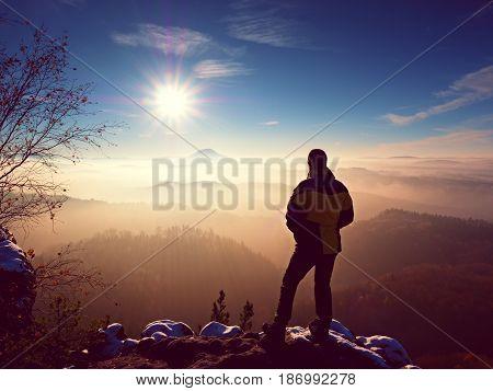 Tall Hiker In Black On Rocky Peak Watch The World . Heavy Orange Mist Bellow