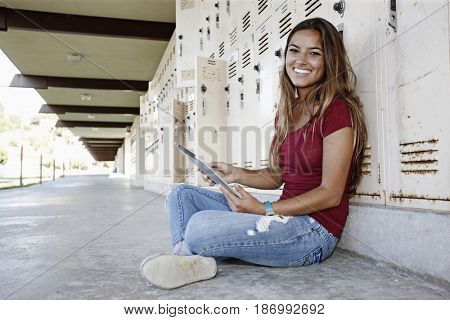 Caucasian teenager sitting on ground using digital tablet