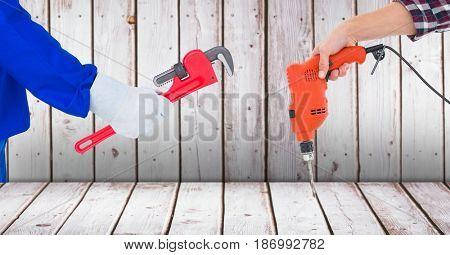 Digital composite of Carpenter hands holding tools against wood