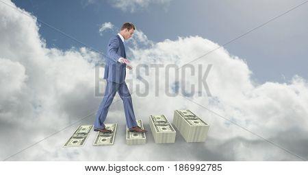 Digital composite of Digital composite image of businessman walking on money steps in sky
