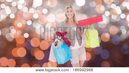 Digital composite of Smiling woman with shopping bags and boxes over bokeh