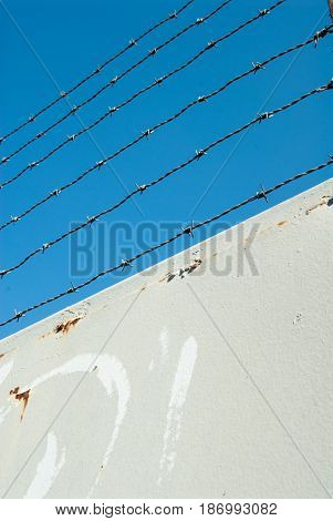 barbed wire on a metal gate blue sky in the background