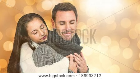 Digital composite of Woman with eyes closed embracing man during winter