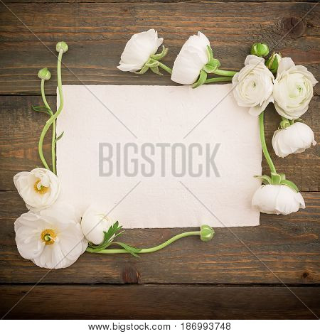 Paper post card and white flowers on wooded background. Flat lay, top view. Vintage background.