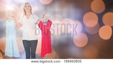 Digital composite of Smiling woman choosing dress over bokeh