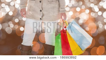 Digital composite of Midsection of woman holding colorful shopping bags