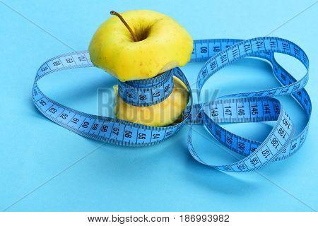 Bitten Apple Wrapped By Blue Measure Tape