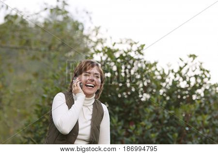 Smiling Hispanic woman talking on cell phone