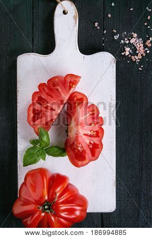 Whole and sliced organic tomatoes Coeur De Boeuf. Beefsteak tomato with pink salt and basil on white wooden chopping board over dark wood background. Top view with space.