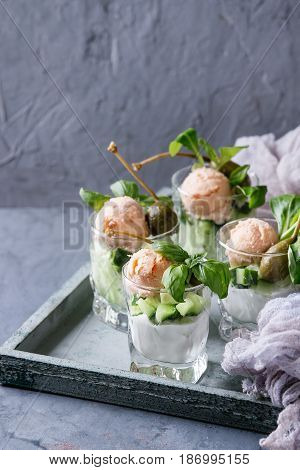 Verrines appetizer with salmon pate, red caviar, cucumber, cream cheese, herbs, capers in glasses served on wooden over blue gray texture background.