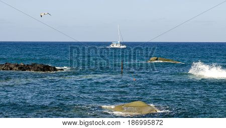 White catamaran among the waves of the Mediterranean sea