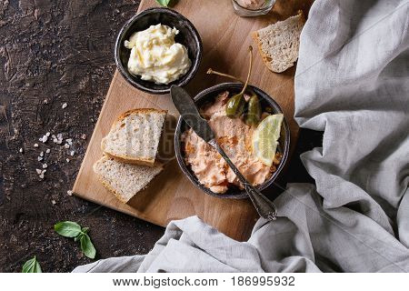 Black bowl of salmon pate with red caviar served with butter, sliced bread, capers, vintage knife and herbs on wooden serving board with textile linen over brown texture background. Top view.