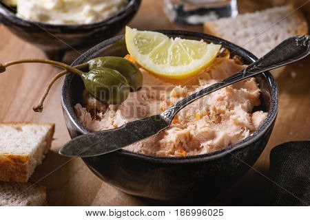 Black bowl of salmon pate with red caviar served with butter, sliced bread, capers, vintage knife and herbs on wooden serving board with textile linen over brown texture background. Close up