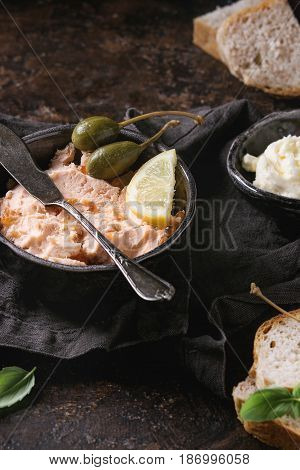 Black bowl of salmon pate with red caviar served with butter, sliced bread, capers, vintage knife and herbs on textile linen napkin over brown texture background. Close up