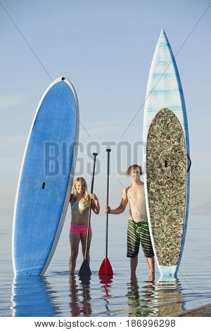 Caucasian couple standing on beach with paddle boards