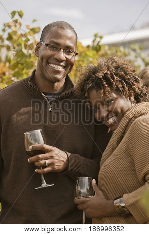Black couple drinking wine in vineyard