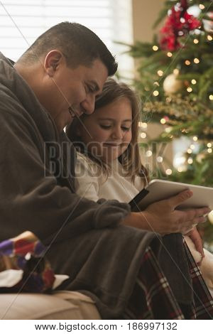 Father and daughter looking at digital tablet on Christmas morning