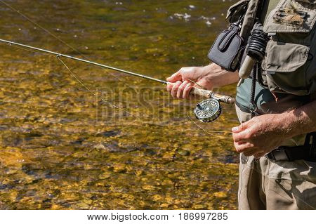 An unknown fisherman with a rod of trout fly on a river Otava Czech Republic. Detail of hand and rod.