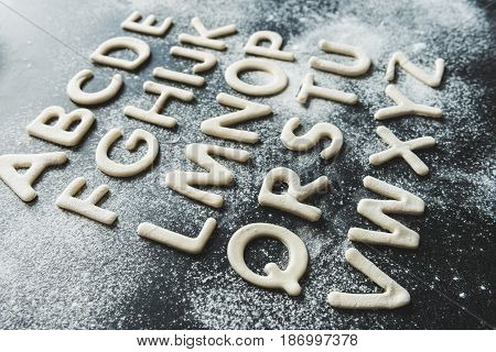 Close Up Of Dough For Cookies In Forms Of Letters With Powdered Sugar, Cookie Dough