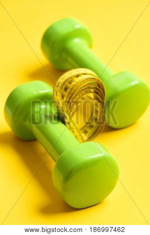 Dumbbells in green color with centimeter on yellow background selective focus