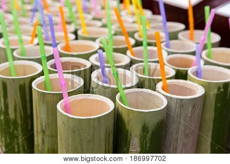 bamboo tube and colorful plastic drinking straws inside