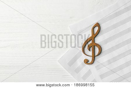 Wooden musical clef lying on music sheet on white wooden background
