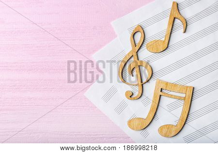 Musical notes lying on music sheets on pink wooden background