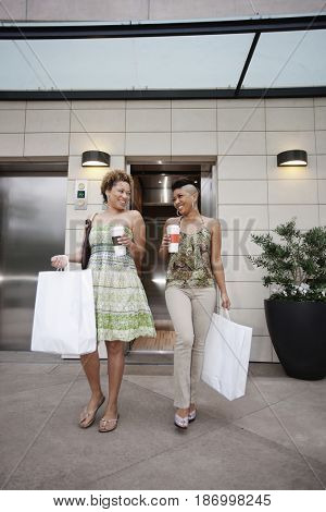 Friends carrying shopping bags and coffee