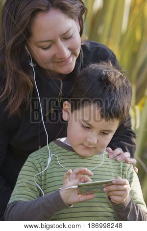 Chilean mother and son listening to mp3 player together