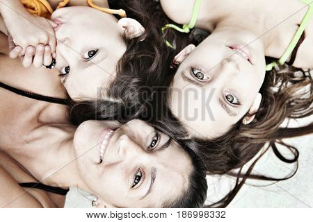 Mother and daughters laying on floor together