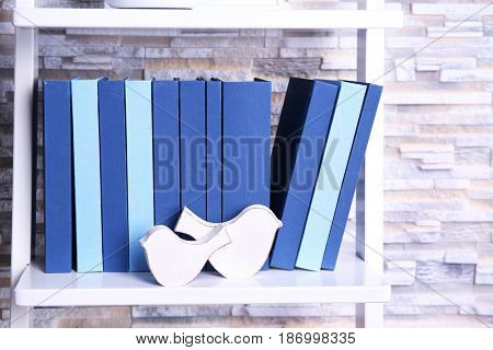 Books and decorations on white shelf at home
