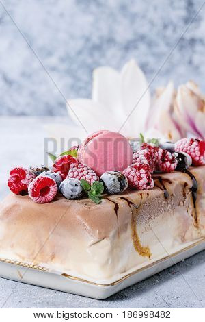 Three layers vanilla, coffee and chocolate ice cream cake, served with frozen berries and macaroons biscuits on rectangular white plate, textile napkin over gray texture background. Close up