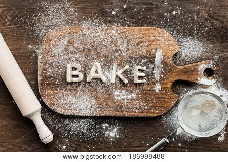 Top View Of Edible Lettering Bake Made From Dough On Wooden Cutting Board, Baking Cookies Concept