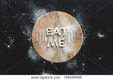 Top View Of Edible Lettering Eat Me From Dough On Wooden Cutting Board, Baking Cookies Concept
