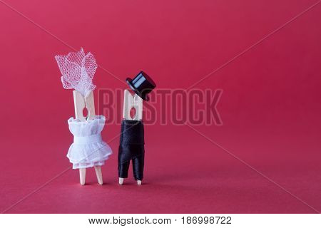 Bride groom wedding invitation card template. Clothespin characters in love. Pink violet paper background copy space. Abstract woman in white dress, man black suit hat. Macro view, selective focus.